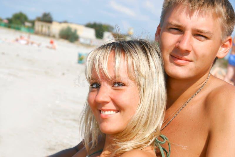 Pares jovenes en la playa fotografía de archivo libre de regalías