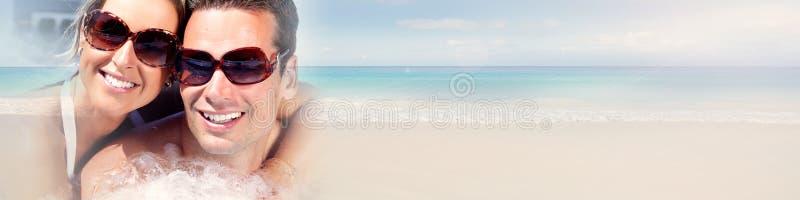 Pares jovenes en la playa imagenes de archivo