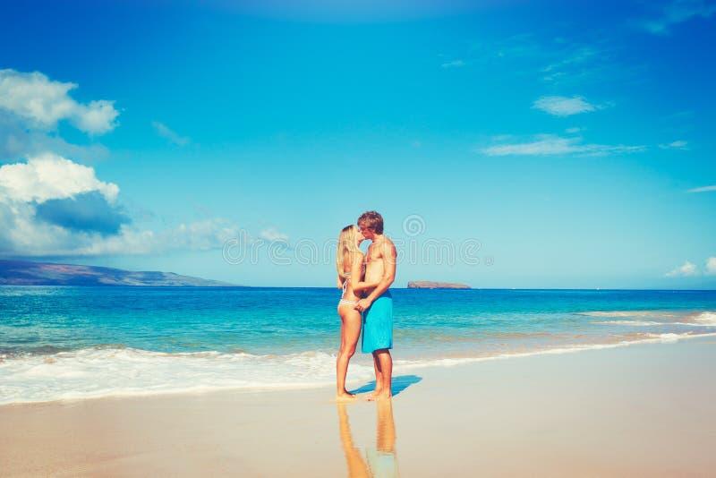 Pares jovenes en la playa tropical imagenes de archivo