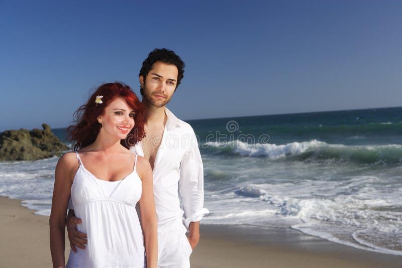 Pares jovenes en la presentación de la playa fotografía de archivo