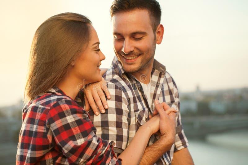 Pares jovenes en la puesta del sol que se ama, al aire libre foto de archivo libre de regalías