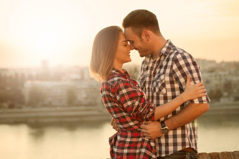 Pares jovenes en la puesta del sol que se ama, al aire libre imagenes de archivo