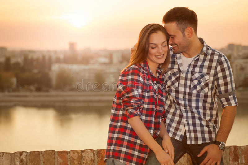 Pares jovenes en la puesta del sol que se ama, al aire libre imagen de archivo libre de regalías