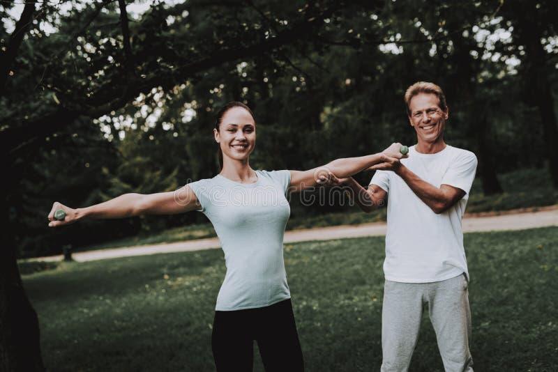Pares jovenes en la ropa de deportes que hace yoga en parque imágenes de archivo libres de regalías