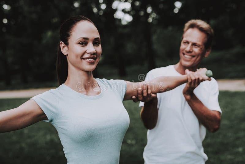 Pares jovenes en la ropa de deportes que hace yoga en parque fotografía de archivo libre de regalías