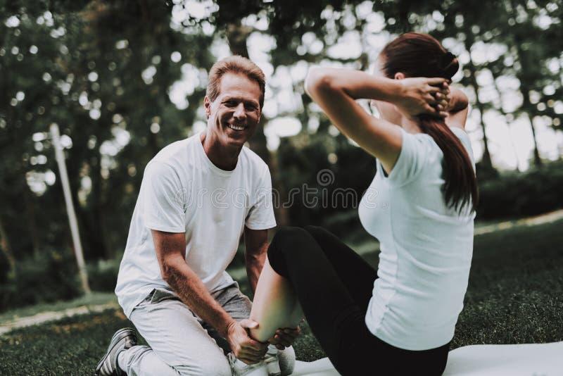 Pares jovenes en la ropa de deportes que hace yoga en parque imagen de archivo libre de regalías