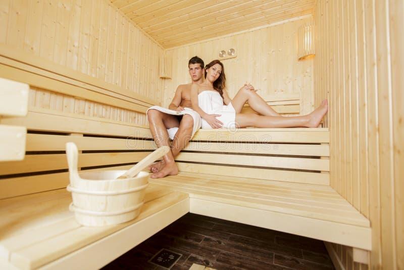 Pares jovenes en la sauna fotografía de archivo libre de regalías