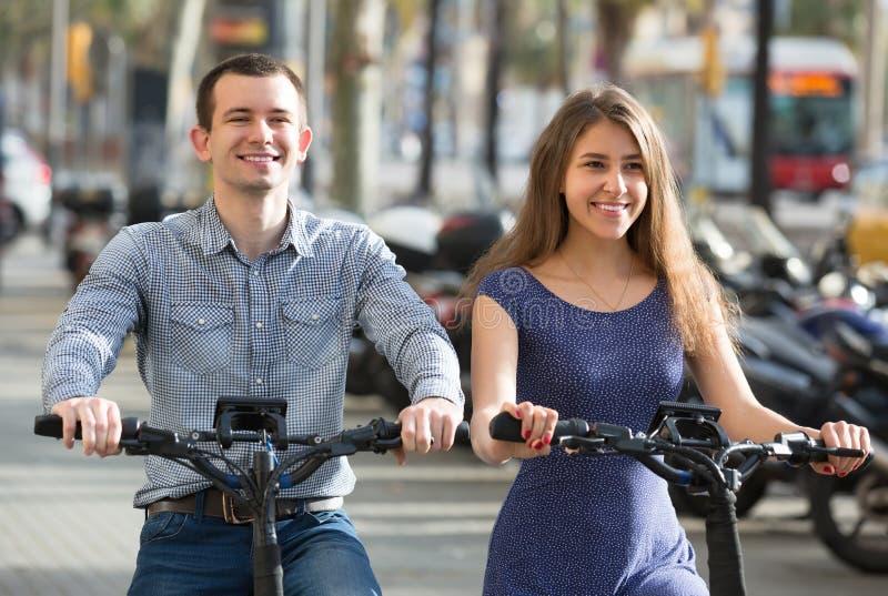 Pares jovenes en las bicis eléctricas fotografía de archivo