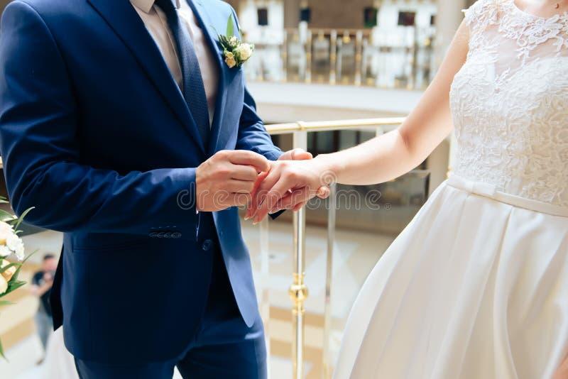 Pares jovenes en los anillos de bodas del oro del intercambio de los recienes casados del amor 1 imagenes de archivo