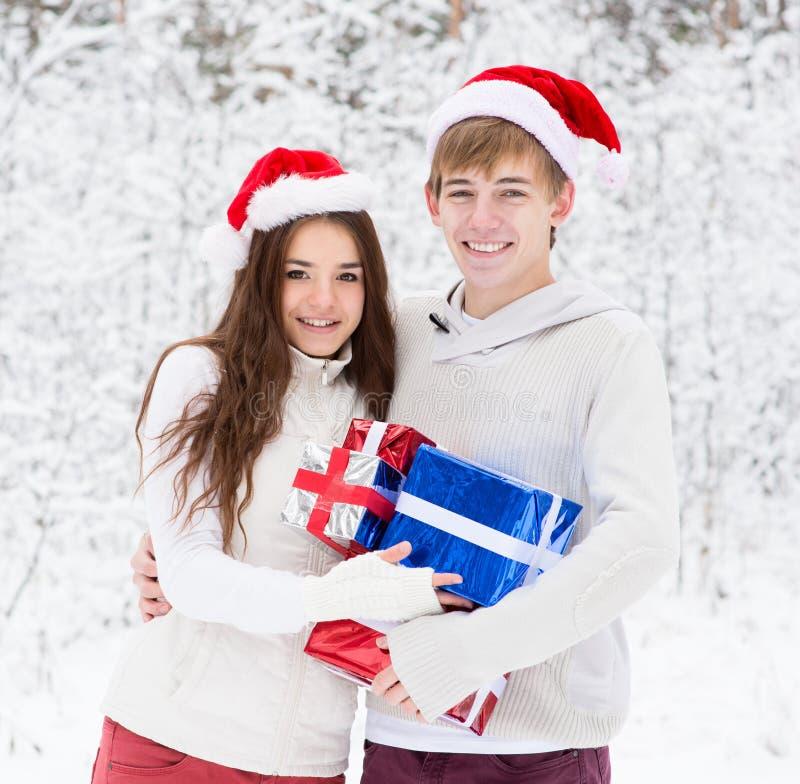 Pares jovenes en los sombreros de Papá Noel que abrazan y que sostienen los regalos fotografía de archivo