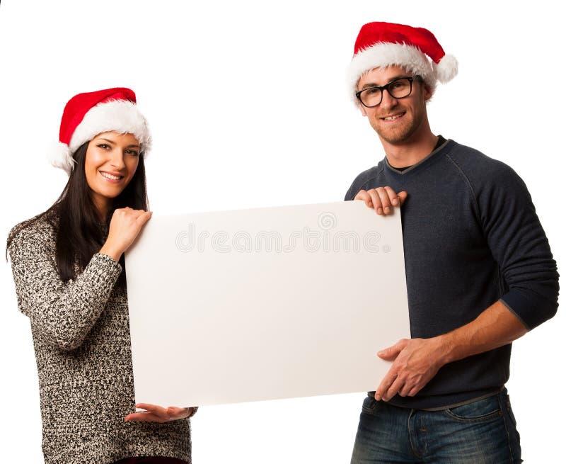 Pares jovenes en los sombreros de santa que llevan a cabo al tablero en blanco para el anuncio fotografía de archivo