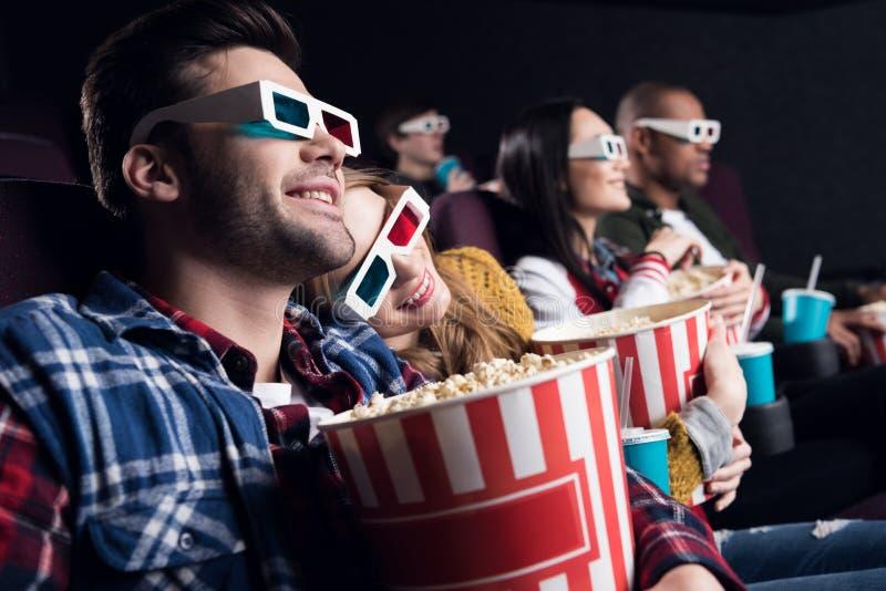 pares jovenes en los vidrios 3d con palomitas y película de observación de la soda fotos de archivo