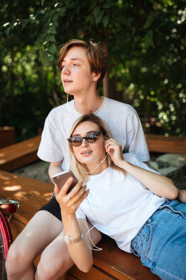 Pares jovenes en música que escucha de los auriculares mientras que pasa tiempo en parque Muchacho pensativo que se sienta en ban imagen de archivo libre de regalías
