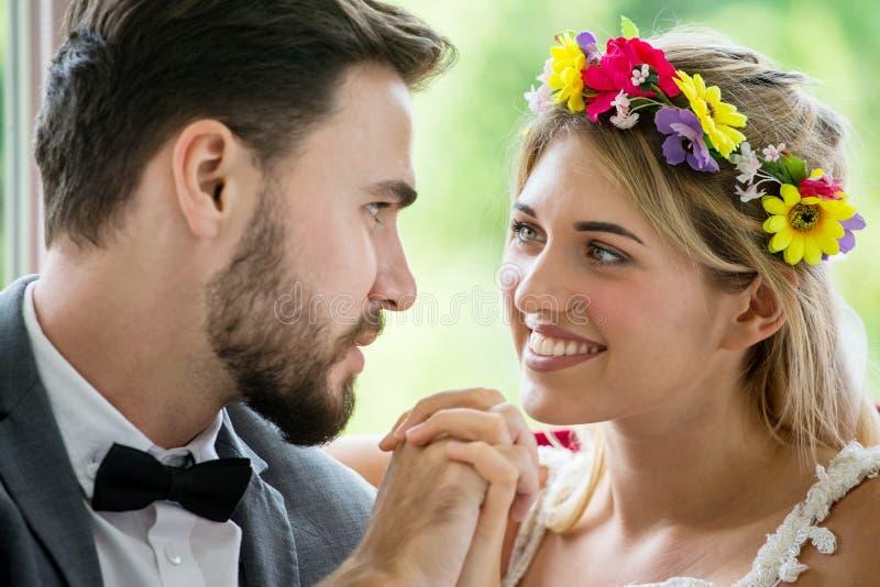 pares jovenes en mano de la tenencia de novia y del novio de la boda del amor junto y mirando uno a newlyweds Retrato del primer  imágenes de archivo libres de regalías