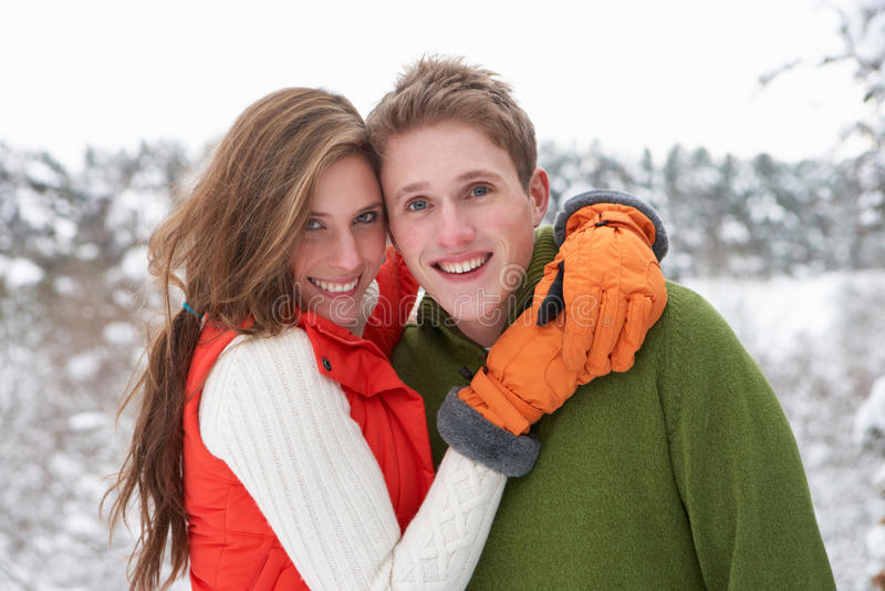 Pares jovenes en nieve imagen de archivo