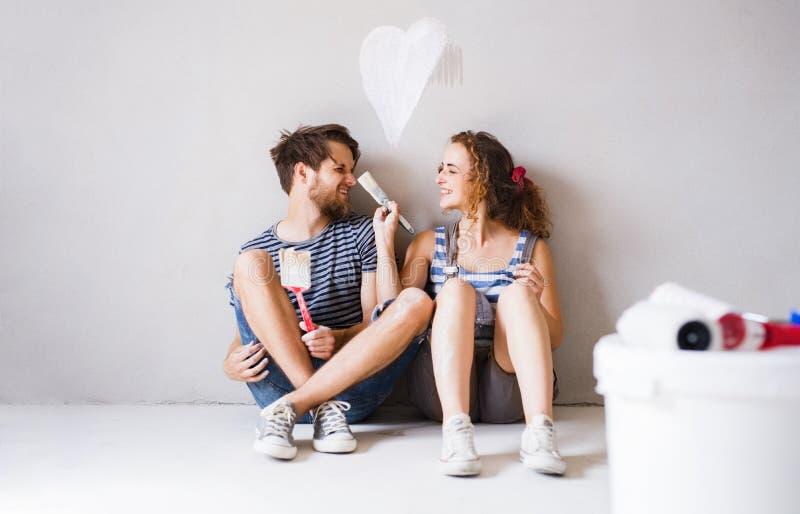 Pares jovenes en paredes de la pintura del amor en su nuevo hogar fotos de archivo libres de regalías