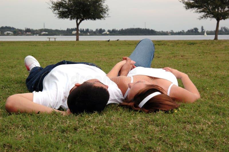 Pares jovenes en parque foto de archivo libre de regalías