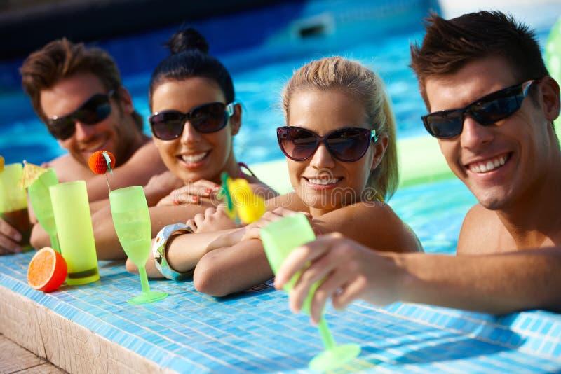 Pares jovenes en piscina con el coctel foto de archivo libre de regalías