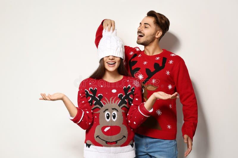Pares jovenes en suéteres de la Navidad imagen de archivo