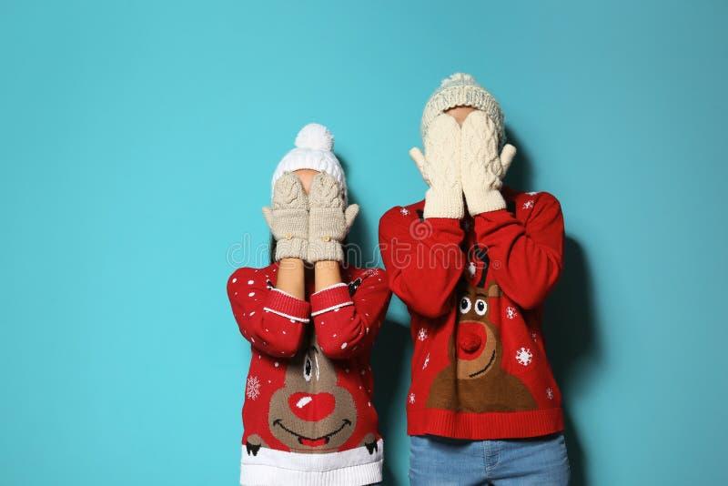 Pares jovenes en suéteres de la Navidad y sombreros hechos punto fotografía de archivo libre de regalías