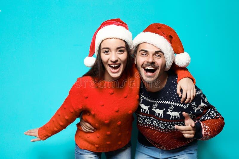 Pares jovenes en suéteres y sombreros calientes de la Navidad imagen de archivo libre de regalías