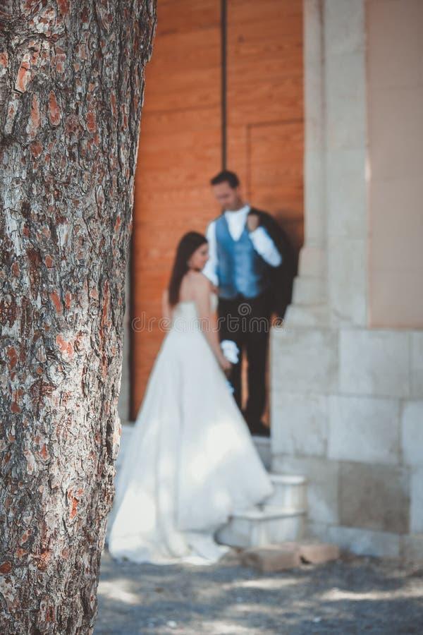 Pares jovenes en su día que se casa, en una escalera grande imagen de archivo