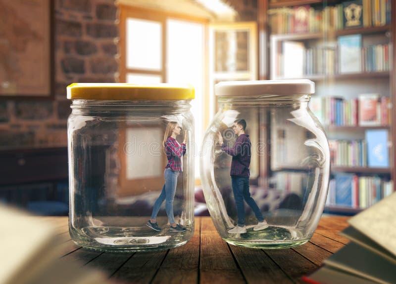 Pares jovenes en tarros de cristal grandes, concepto de la soledad imagen de archivo
