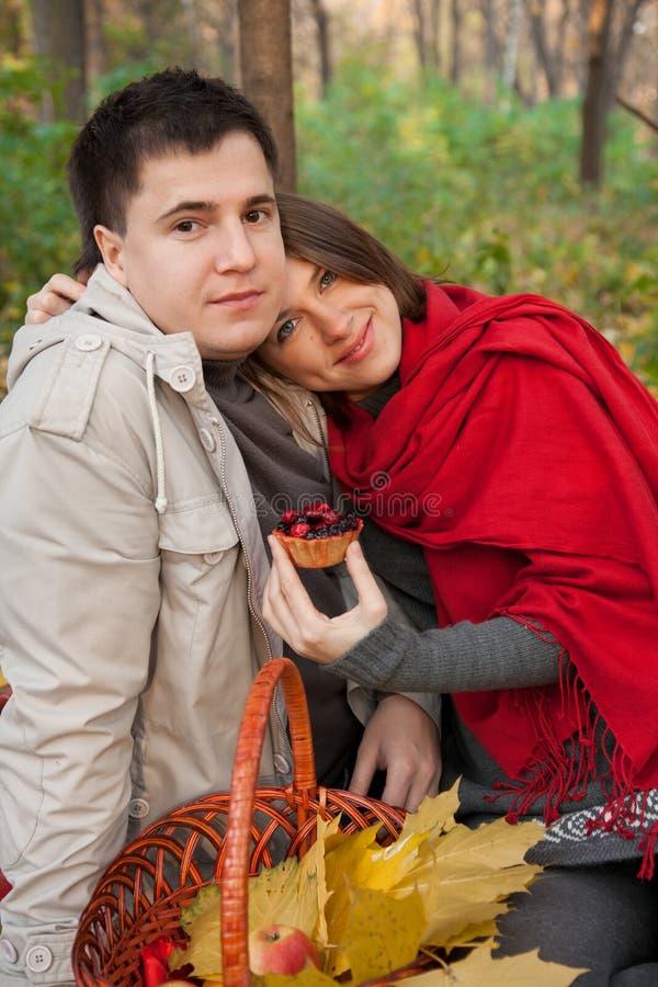 Pares jovenes en un área de comida campestre del bosque del otoño fotografía de archivo libre de regalías