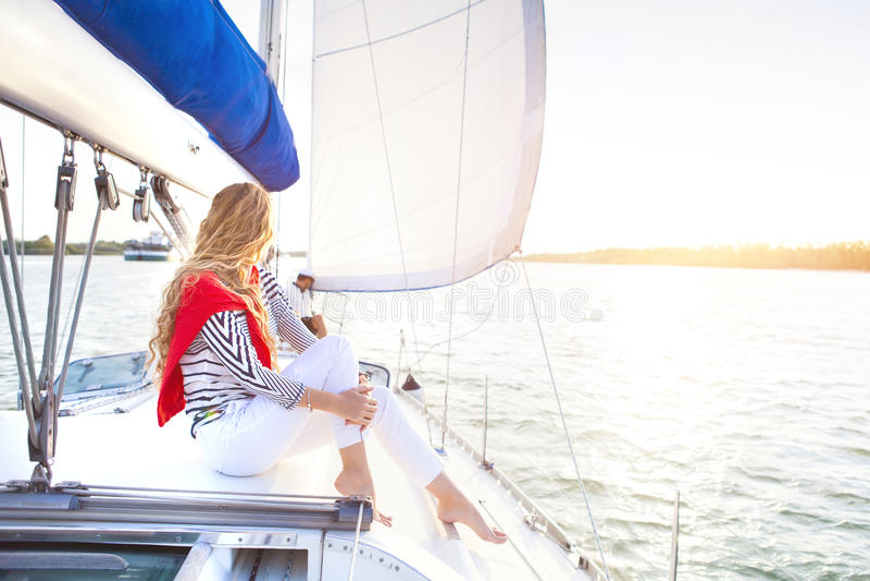 Pares jovenes en un barco de navegación en el verano imagen de archivo libre de regalías