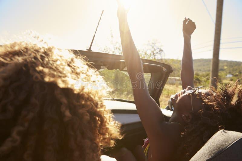 Pares jovenes en un coche de tragante abierto, mujer con los brazos aumentados foto de archivo libre de regalías