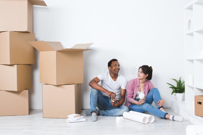 Pares jovenes en un hogar móvil de la decoración del planeamiento de nueva casa foto de archivo