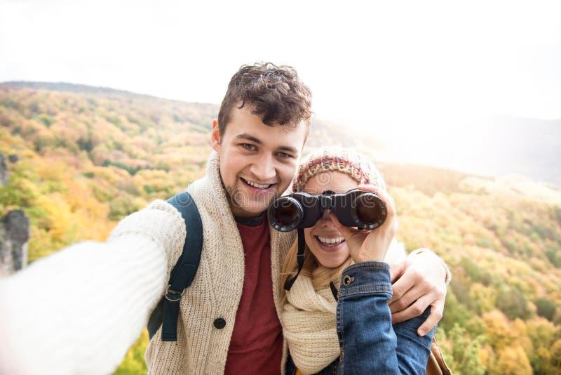 Pares jovenes en un paseo en el bosque del otoño que toma el selfie imagenes de archivo