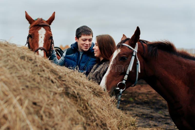 Pares jovenes en un pueblo ruso con los caballos, montando foto de archivo