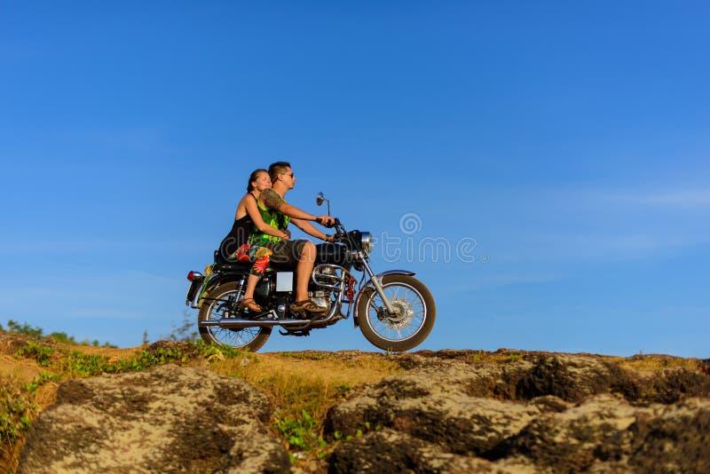 Pares jovenes en una motocicleta en la tierra rocosa Individuo feliz y muchacha que viajan en una moto foto de archivo libre de regalías
