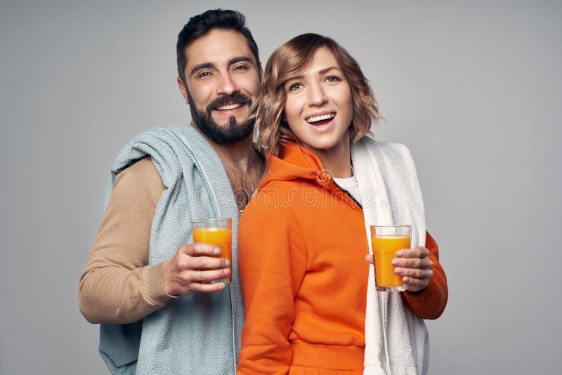 Pares jovenes en vidrios que se sostienen casuales de zumo de naranja foto de archivo libre de regalías