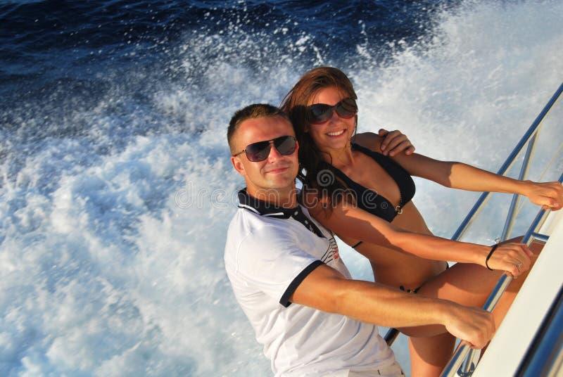 Pares jovenes en yate del barco de vela de la navegación del amor imágenes de archivo libres de regalías