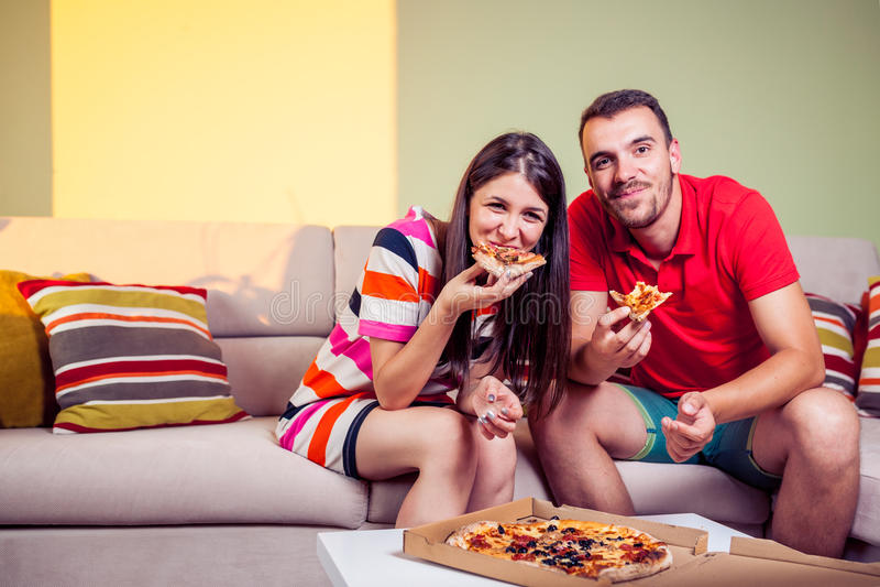 Pares jovenes enrrollados que comen la pizza en un sofá imagen de archivo libre de regalías
