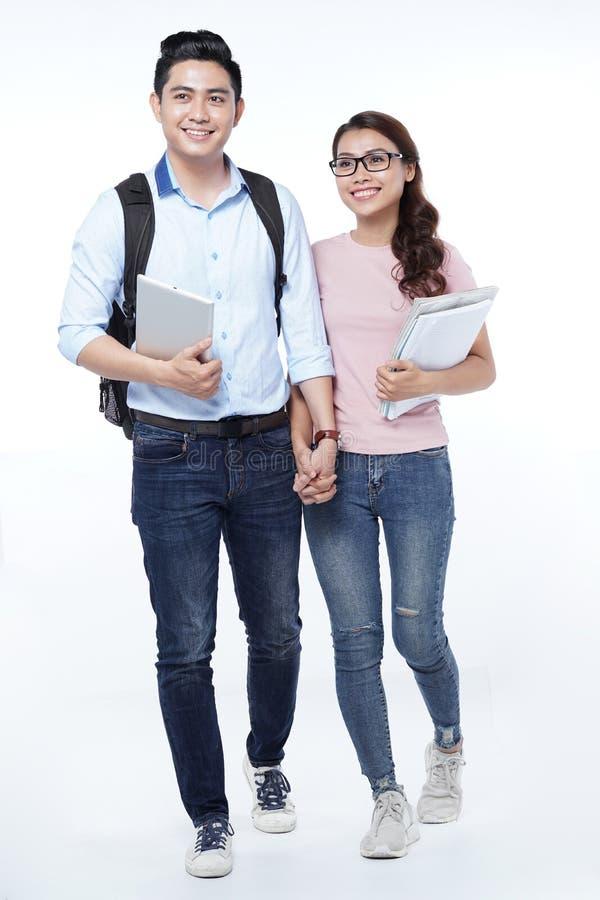 Pares jovenes felices asiáticos del estudiante que caminan con los libros en las manos, aisladas en el fondo blanco imagen de archivo