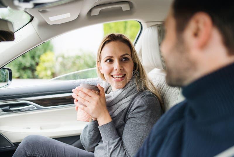 Pares jovenes felices con el café que se sienta en el coche, hablando fotos de archivo