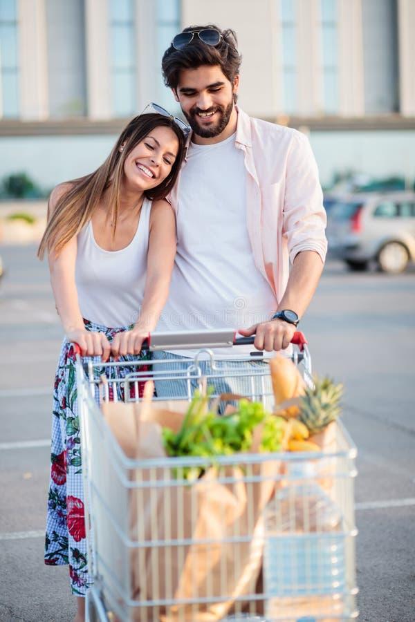 Pares jovenes felices con el carro de la compra lleno delante de la alameda imagenes de archivo