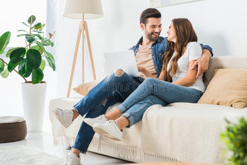 pares jovenes felices con el ordenador portátil que mira uno a en el sofá imagen de archivo libre de regalías