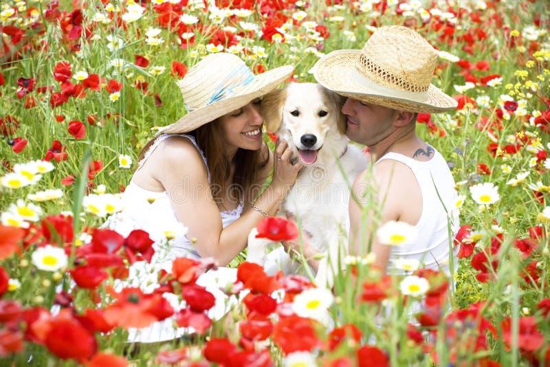 Pares jovenes felices con el perro fotografía de archivo