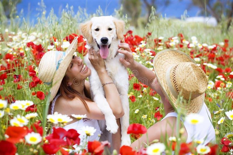 Pares jovenes felices con el perro imágenes de archivo libres de regalías