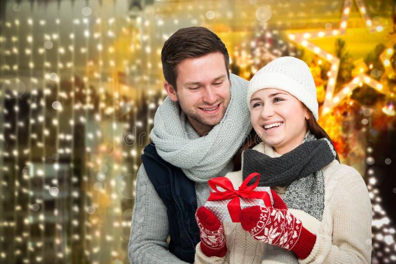 Pares jovenes felices con el regalo de Navidad foto de archivo libre de regalías