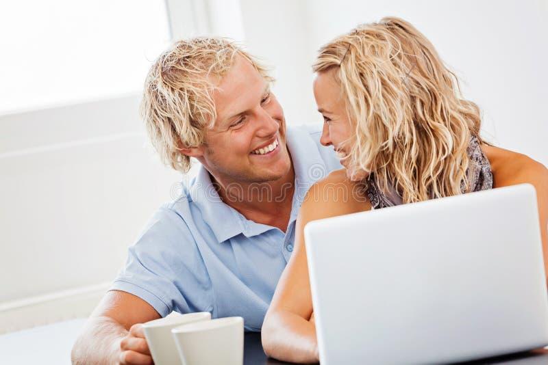Pares jovenes felices con la computadora portátil fotos de archivo