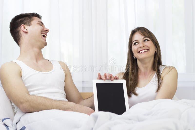 Pares jovenes felices con la tableta digital fotos de archivo