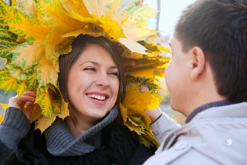 Pares jovenes felices con las hojas de otoño fotografía de archivo libre de regalías