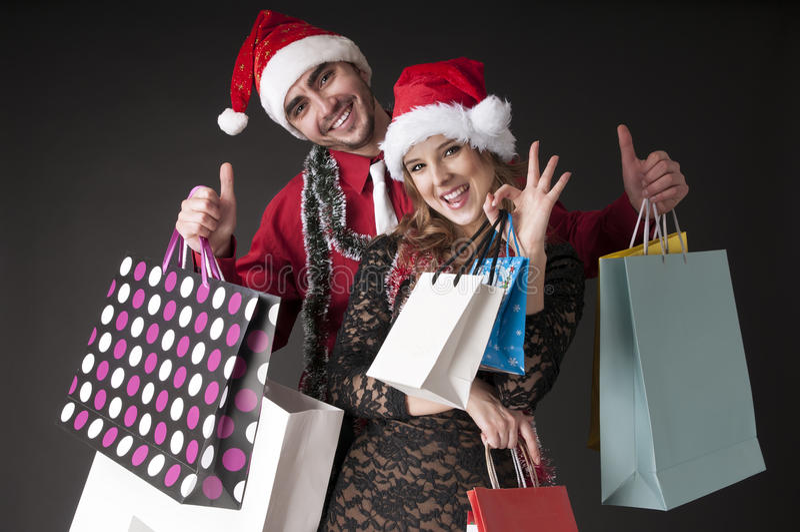 Pares jovenes felices con los bolsos de compras. fotos de archivo libres de regalías
