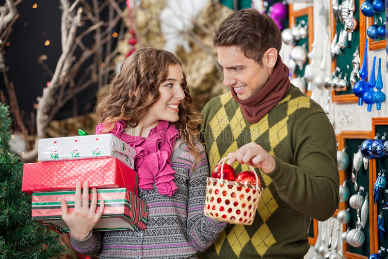 Pares jovenes felices con los presentes en la Navidad fotografía de archivo libre de regalías