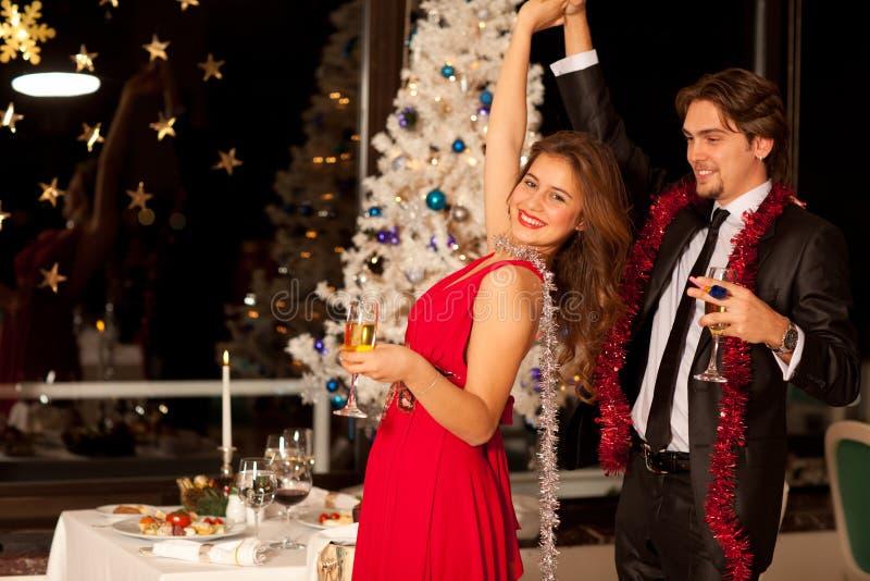 Pares jovenes felices con los vidrios del champán imagen de archivo